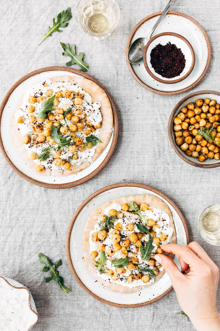 Two plates prepped with Roasted Chicken Pita Wraps with Crispy Chickpeas and Tzatziki are photographed from the top view.