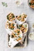 Roasted Chicken Pita Wrap with Crispy Chickpeas and Tzatziki are placed in a basket and photographed from the top view.