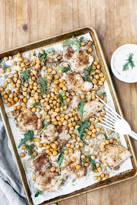 A sheet pan of roasted chicken, chickpeas and arugula with spices is photographed from the top view.
