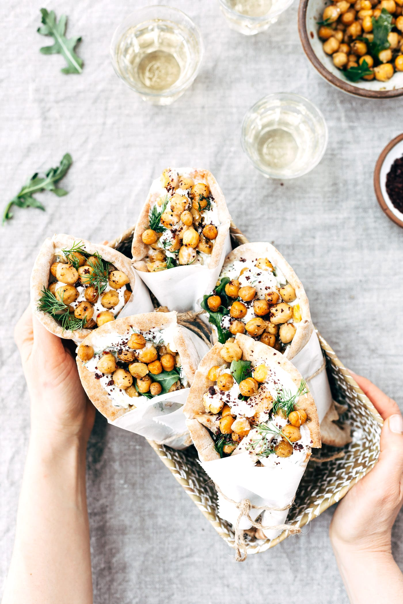Roasted Chicken Pita Wrap with Crispy Chickpeas and Tzatziki are placed in a basket and photographed from the top view as a woman is serving them.