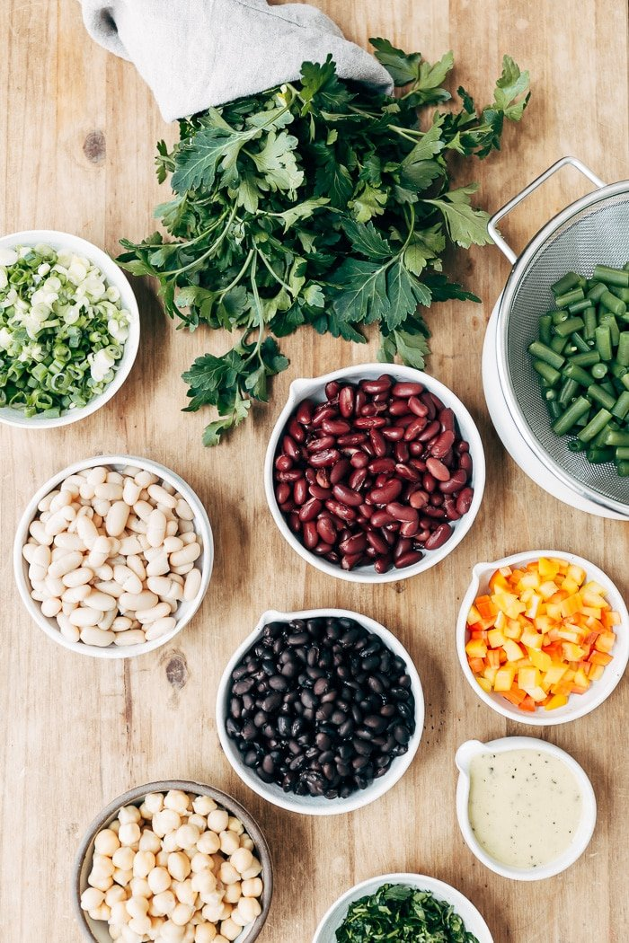 The ingredients (kidney beans, garbanzo beans, green beans, black beans, pepper, and dressing) for five bean salad are photographed from the top view.