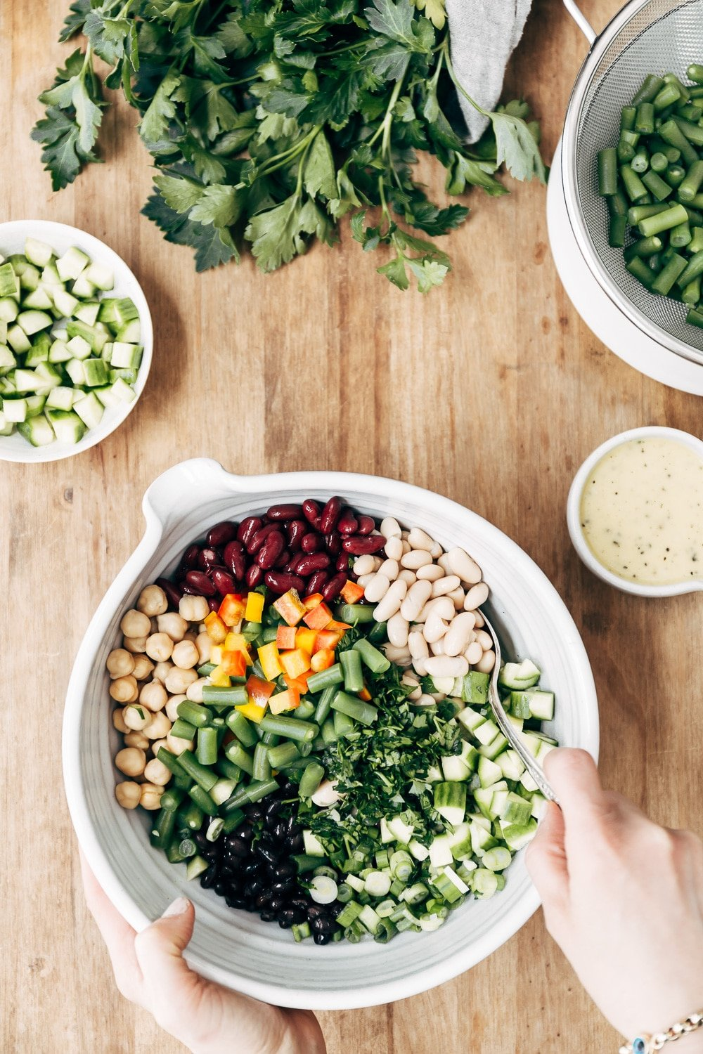 5 Bean Salad Recipe - A woman is photographed from the top view as she is getting ready to mix a bowl of five bean salad.