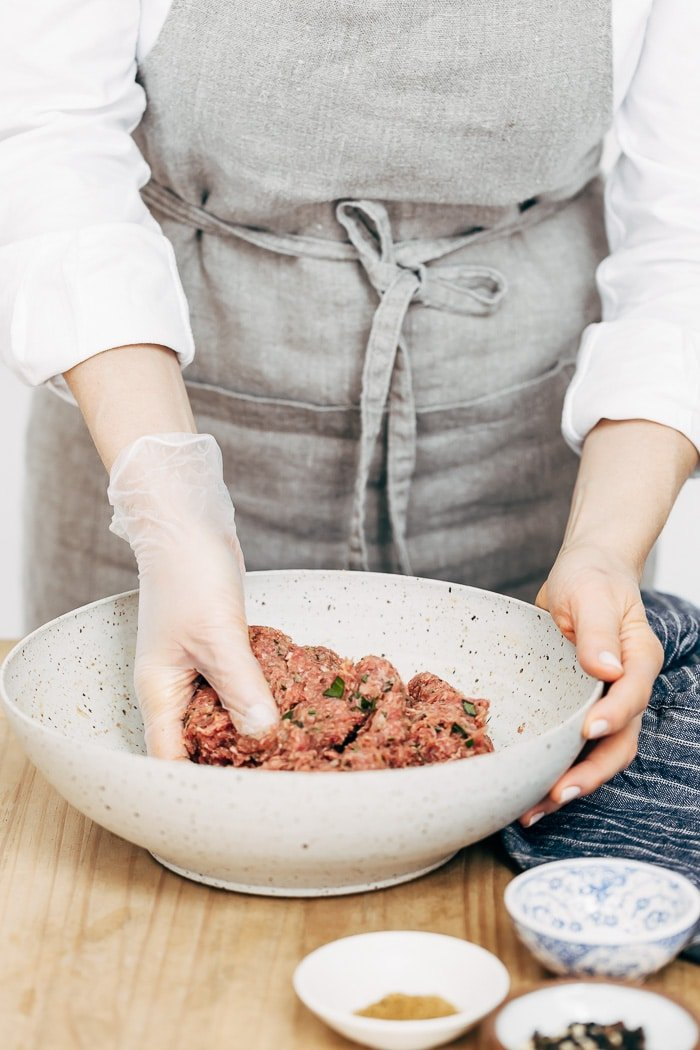 A woman is photographed from the front view as she is mixing the ingredients for Turkish Meatballs.