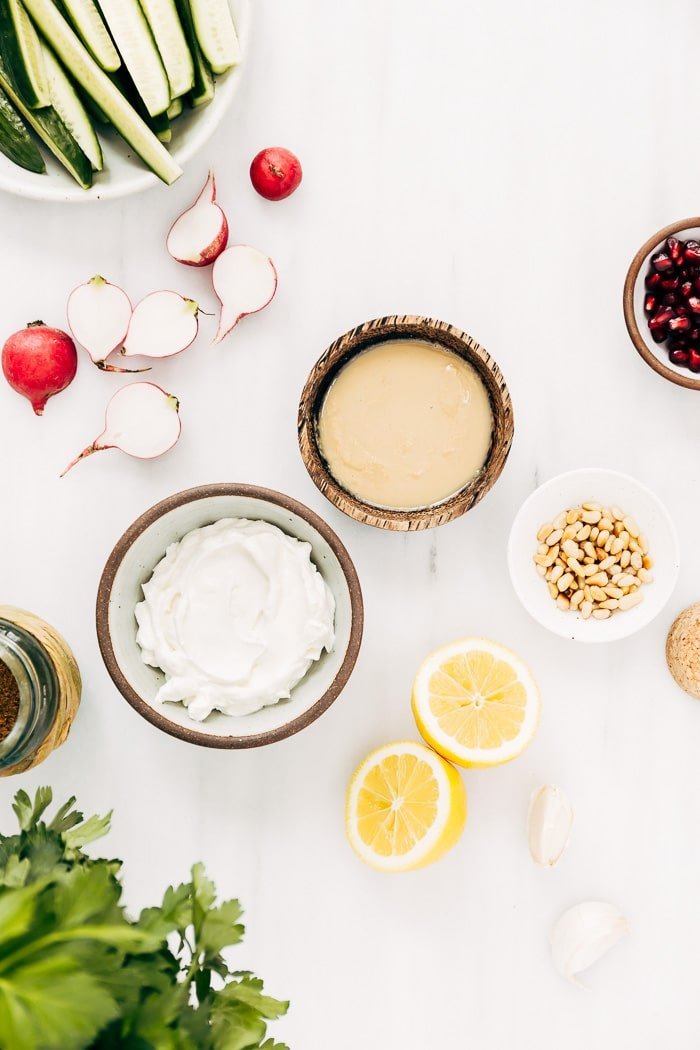Ingredients for tahini yogurt sauce are laid out and photographed from the top view.