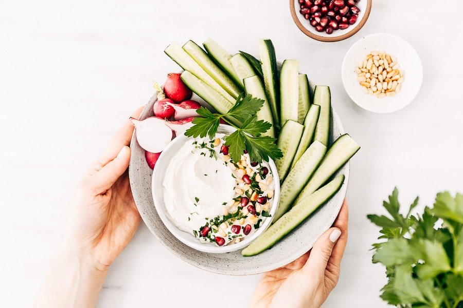 A bowl of tahini yogurt sauce surrounded with cucumbers and radishes is photographed as they are placed on the table by a woman from the top view.