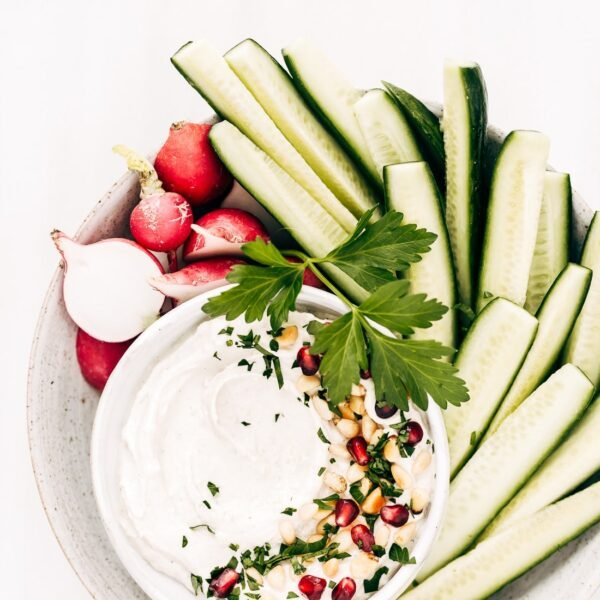 A bowl of tahini yogurt sauce surrounded with cucumbers and radishes is photographed from the top view.