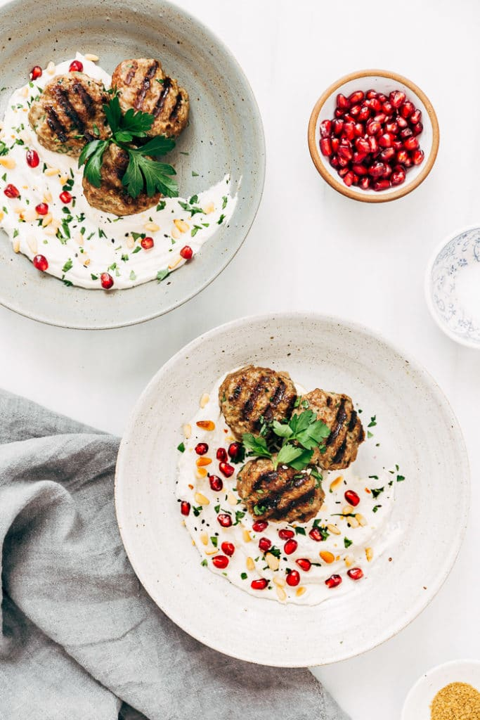 Two bowls filled with yogurt tahini sauce and Turkish meatballs garnished with pomegranate seeds and pine nuts.