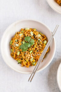 A bowl of sweet potato noodles with cilantro garnish