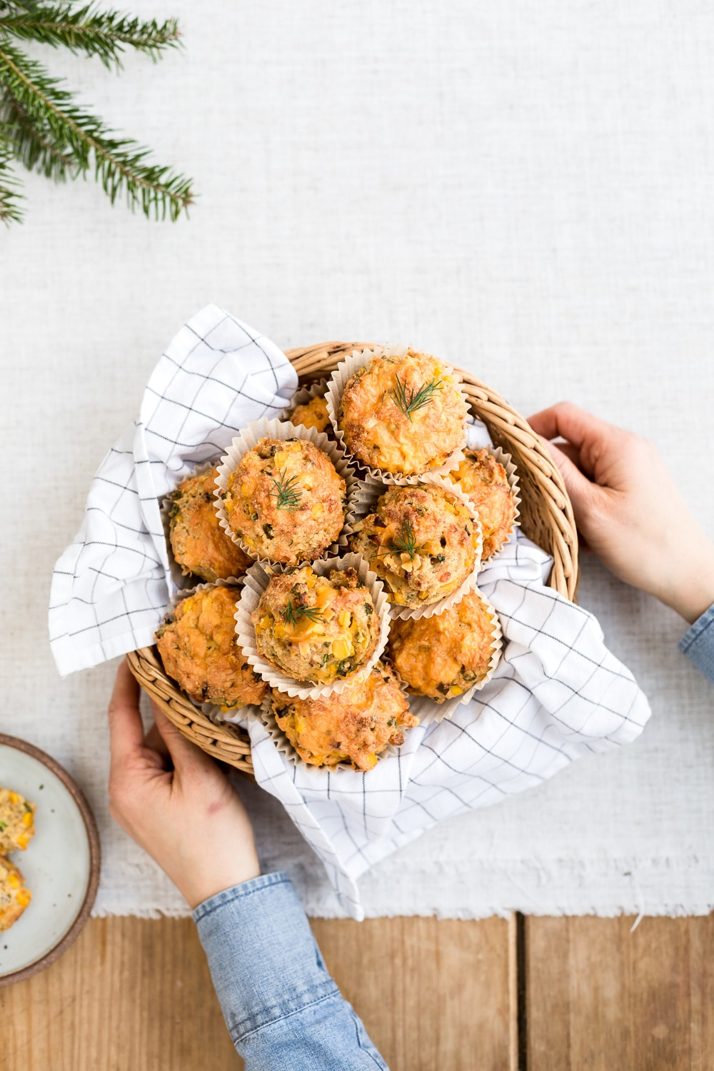 Healthyish Savory Recipes for the Game Day: A woman is photographed from the top view as she is serving Cornbread Muffins with Cheddar and Scallions in a basket lined with cloth.