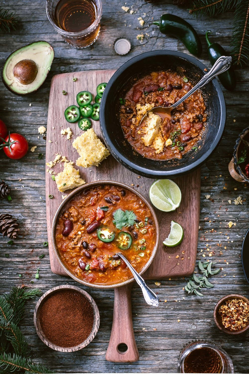 Healthyish Savory Recipes for the Game Day: 2 bowls of Heartwarming Turkey and Bean Chili photographed from the top view along with corn muffins, fresh lime, sliced jalapeno, and avocados.