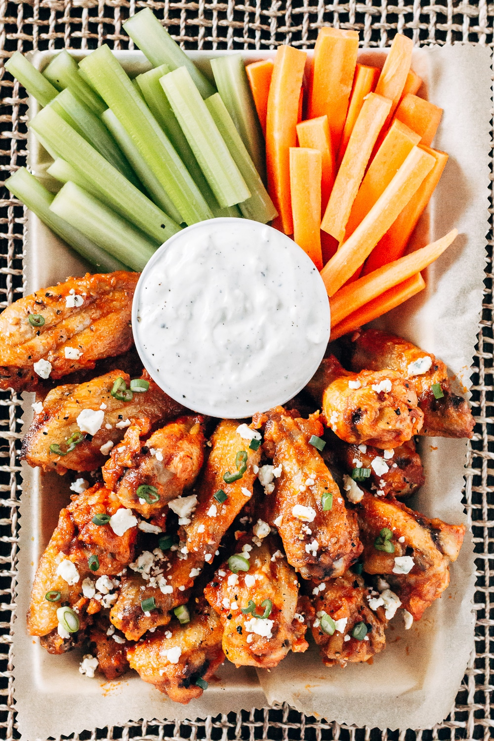 Healthyish Savory Recipes for the Game Day: Oven-Baked Chicken wings with hot wing sauce is served along with carrot sticks, celery, and blue ranch sauce