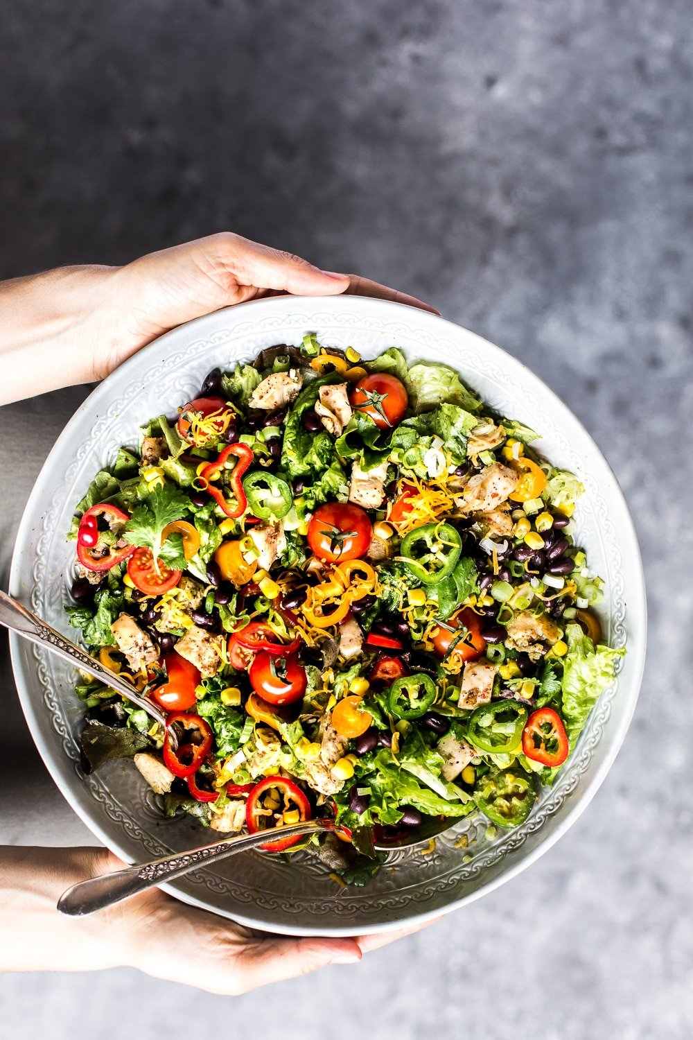 Healthyish Savory Recipes for the Game Day: A woman is photographed from the top view as she is about to serve a big bolw of Southwestern Chicken Salad with Creamy Avocadp Dressing