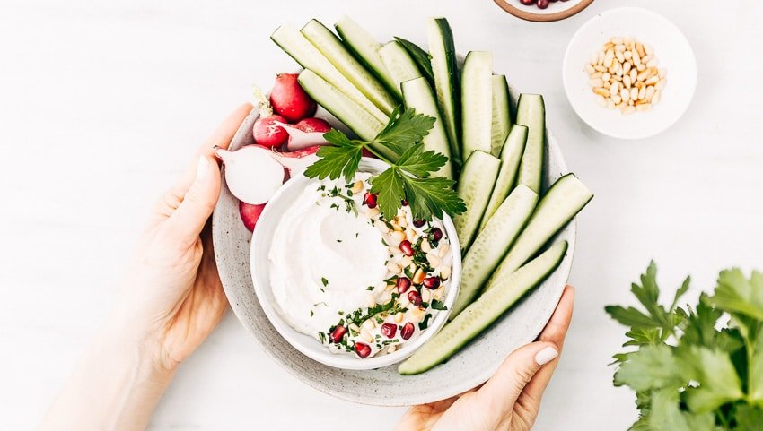A woman is serving a bowl of tahini yogurt sauce photographed from the top view.