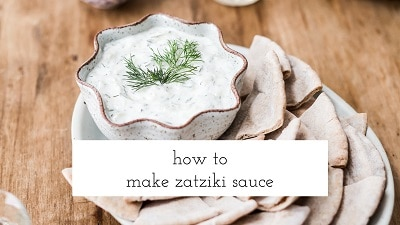 A Bowl of Tzatziki is served with pita bread and photographed from the top view.