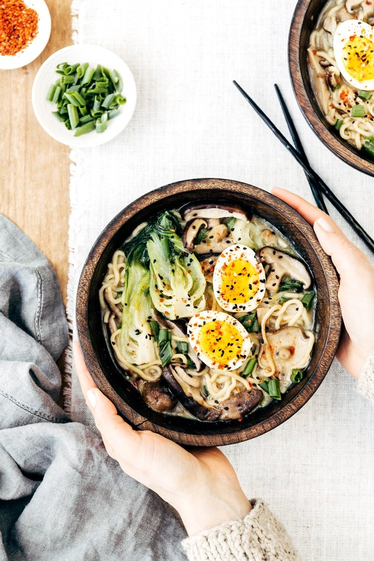 A woman is photographed from the top view as she is serving a bowl of Weeknight Vegetarian Ramen Bowl with Shiitake Mushrooms and Bok Choy