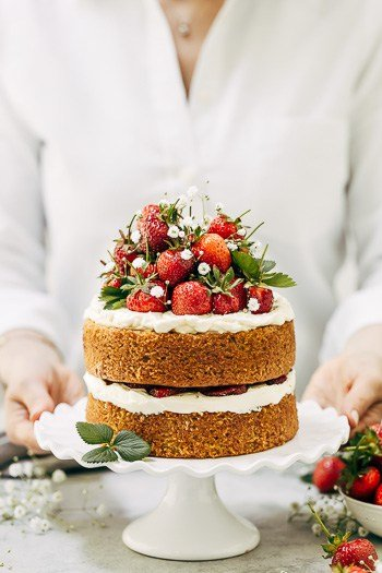 A woman is photographed with strawberry Almond Flour cake.