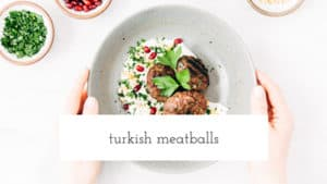 A bowl filled with Turkish Meatballs and yogurt tahini sauce placed on a marble surface and photographed from the top view.