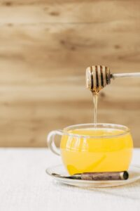 A glass cup full of turmeric ginger tea is being drizzled with honey photographed from the front view.