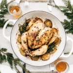 A whole chicken and potato bake in a table setting is photographed from the top view.