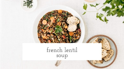 A bowl of French Lentil Soup is photographed from the top view with some bread on the side.