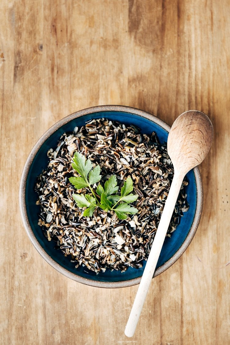 A bowl of cooked wild rice garnished with fresh parsley is photographed from the front view for the how to cook wild rice recipe post