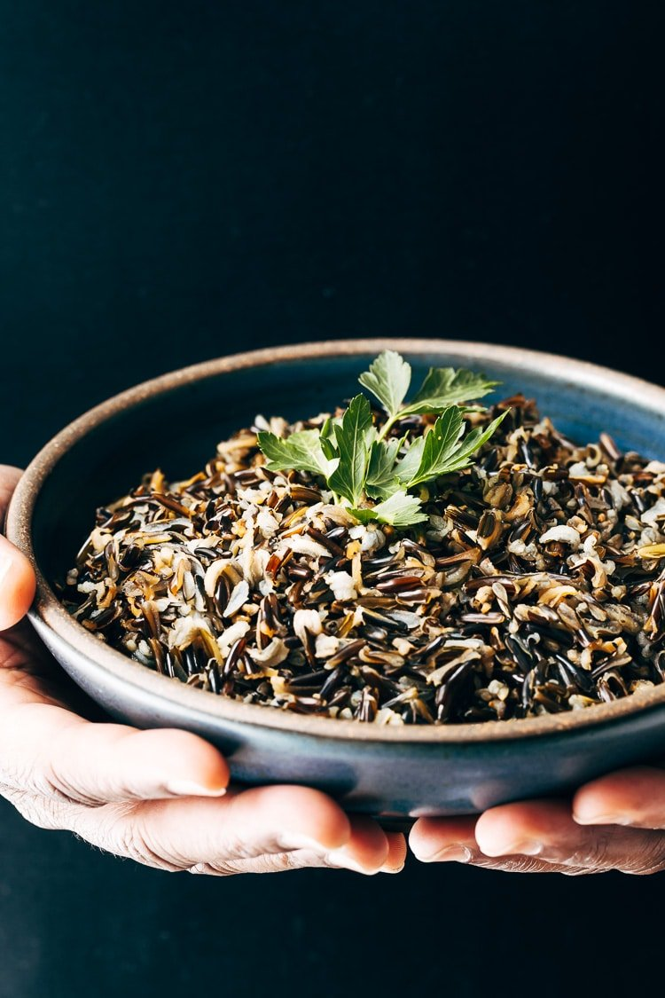 A man is photographed from the front view (close up) with a bowl of cooked wild rice garnished with a few leaves of parsley for the How To Make Wild Rice Recipe post.
