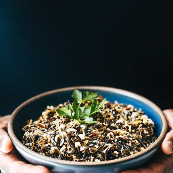 A man is photographed from the front view with a bowl of cooked wild rice garnished with a few leaves of parsley for the How To Make Wild Rice Recipe post.