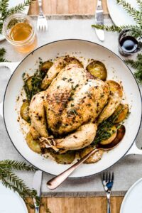 Whole roasted chicken with potatoes in a skillet with a spoon on the side