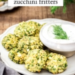 A plate full of Oven-Baked Zucchini Fritters with Feta and Dill are served with yogurt sauce and photographed from the front.