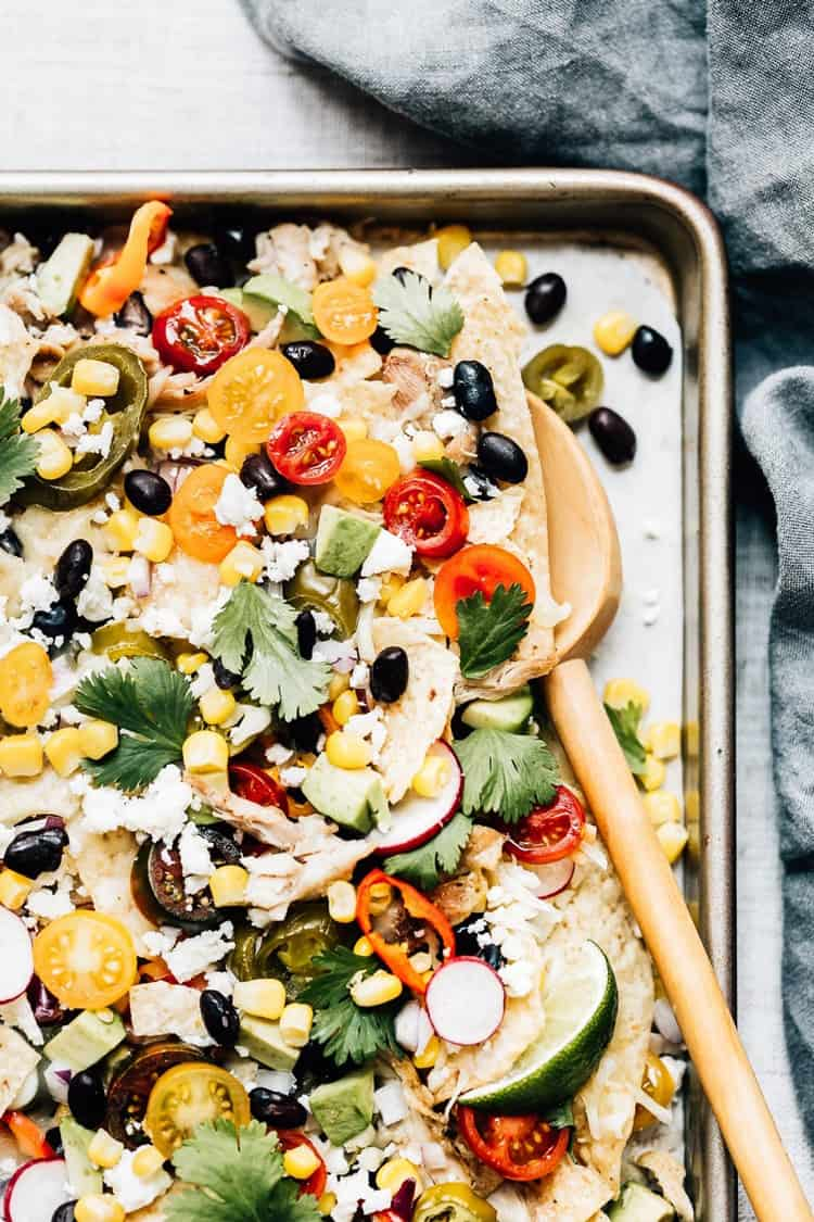 Mexican Food Recipes made easy - Sheet Pan Chicken Nachos with a wooden spoon on the side