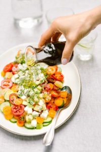 One of the spring salad recipes - A woman is drizzling a cucumber tomato mozzarella salad with balsamic vinaigrette