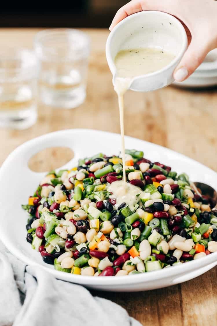 Five bean Salad being drizzled with dressing