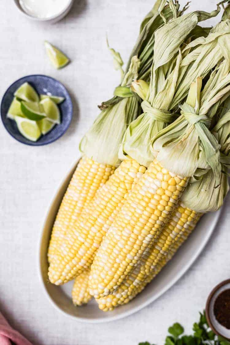 Fresh corn with wedges of lime on the side