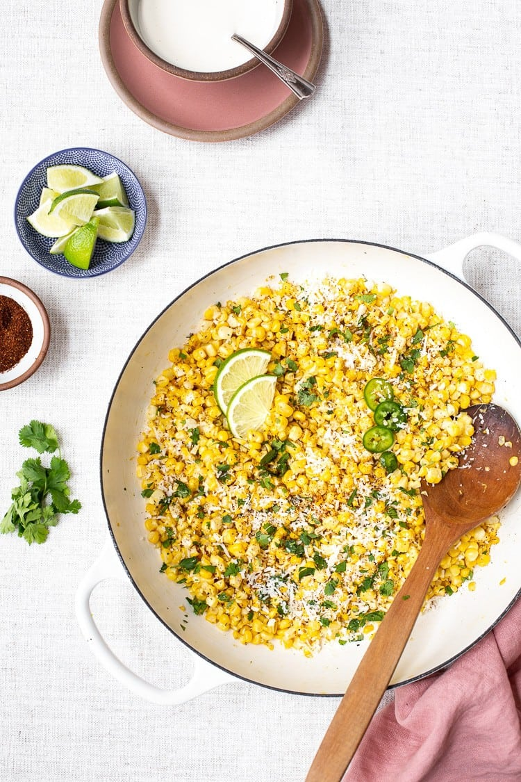 Skillet Mexican Street Corn off the cob in a large skillet with lime and sauce on the side