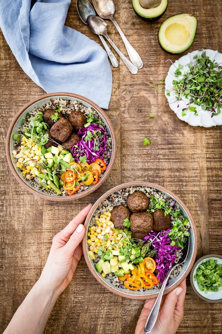 a woman is photographed from the top view as she is serving a few bowls of quinoa power bowl dishes.