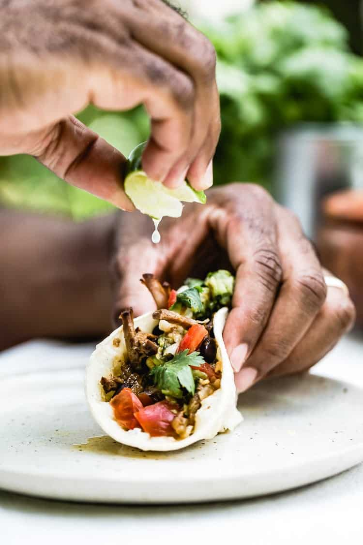 Easy Mexican Recipes for Cinco de Mayo - Slow Cooked Beef Brisket Tacos - A man is drizzling a taco with lime