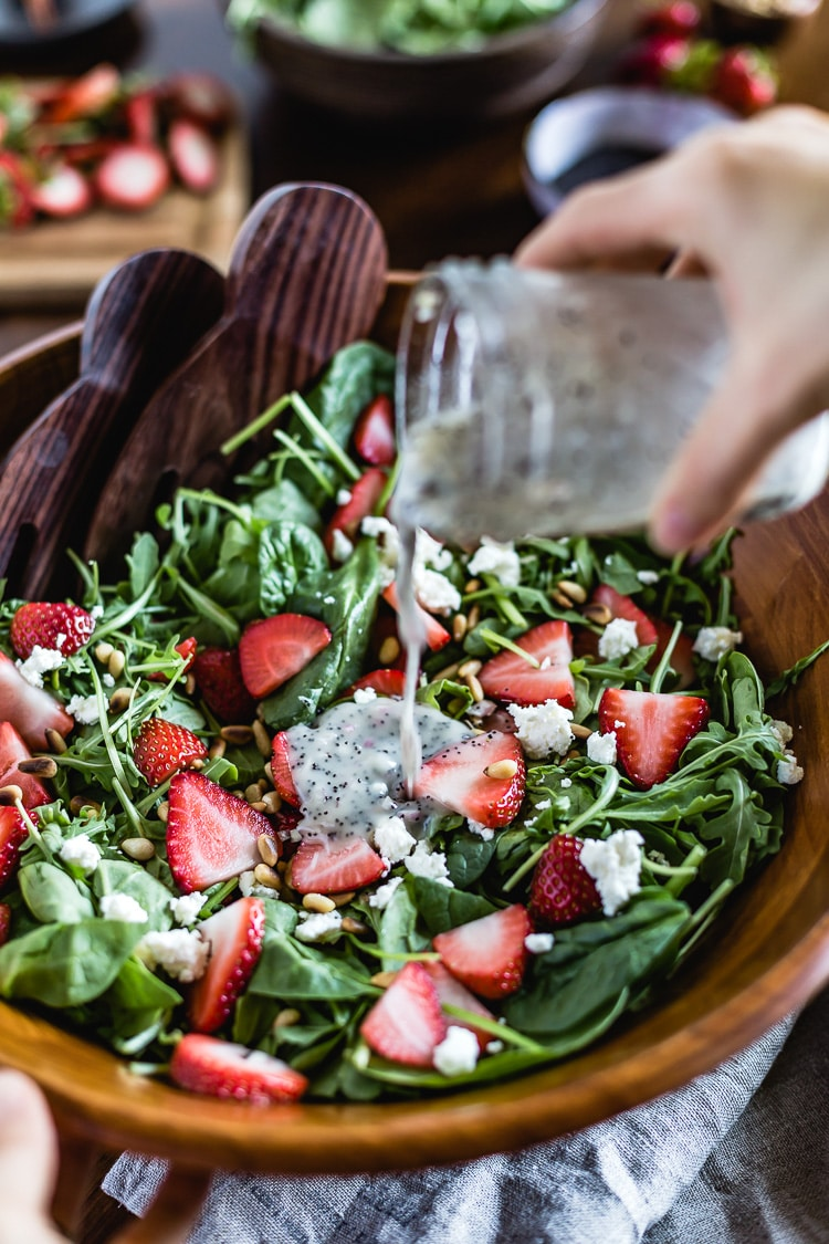 Strawberry Spinach Salad with Poppy Seed Dressing photographed as a person is drizzling it with the dressing from the front.