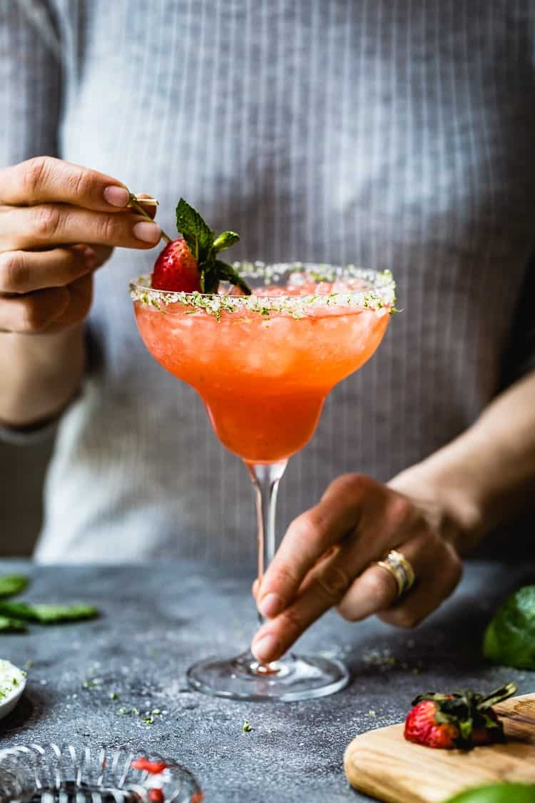 Easy Mexican Margaritas - Strawberry Champagne Margaritas is being garnished with a strawberry