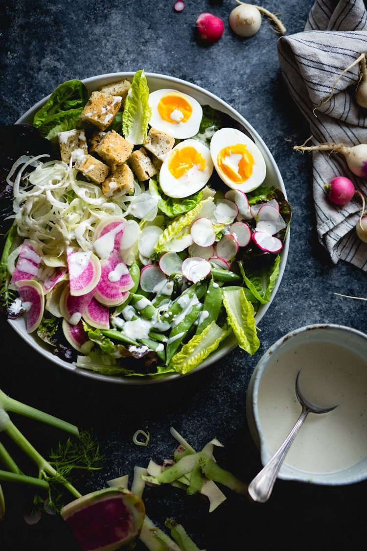 A bowl of Spring Green salad with eggs is photographed from the top view.