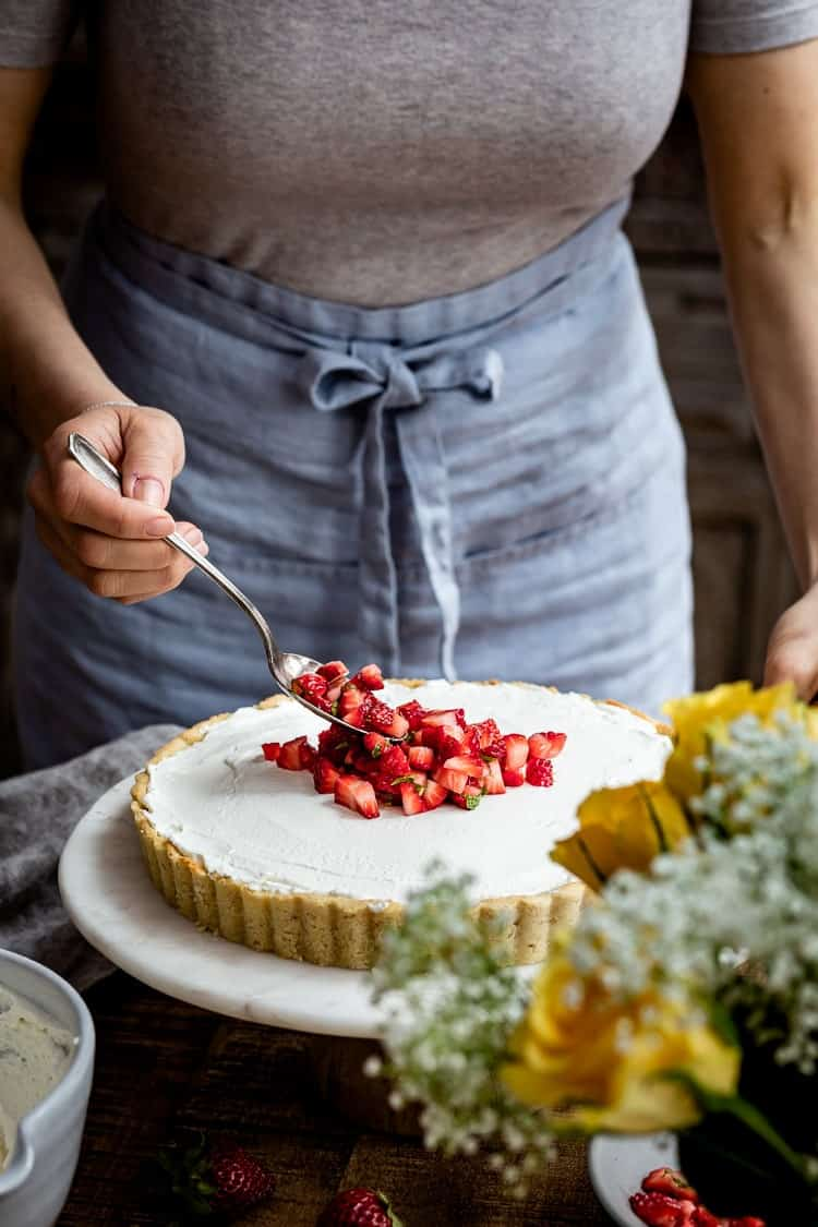 A woman is garnishing Gluten Free Strawberry Mascarpone Tart with strawberries