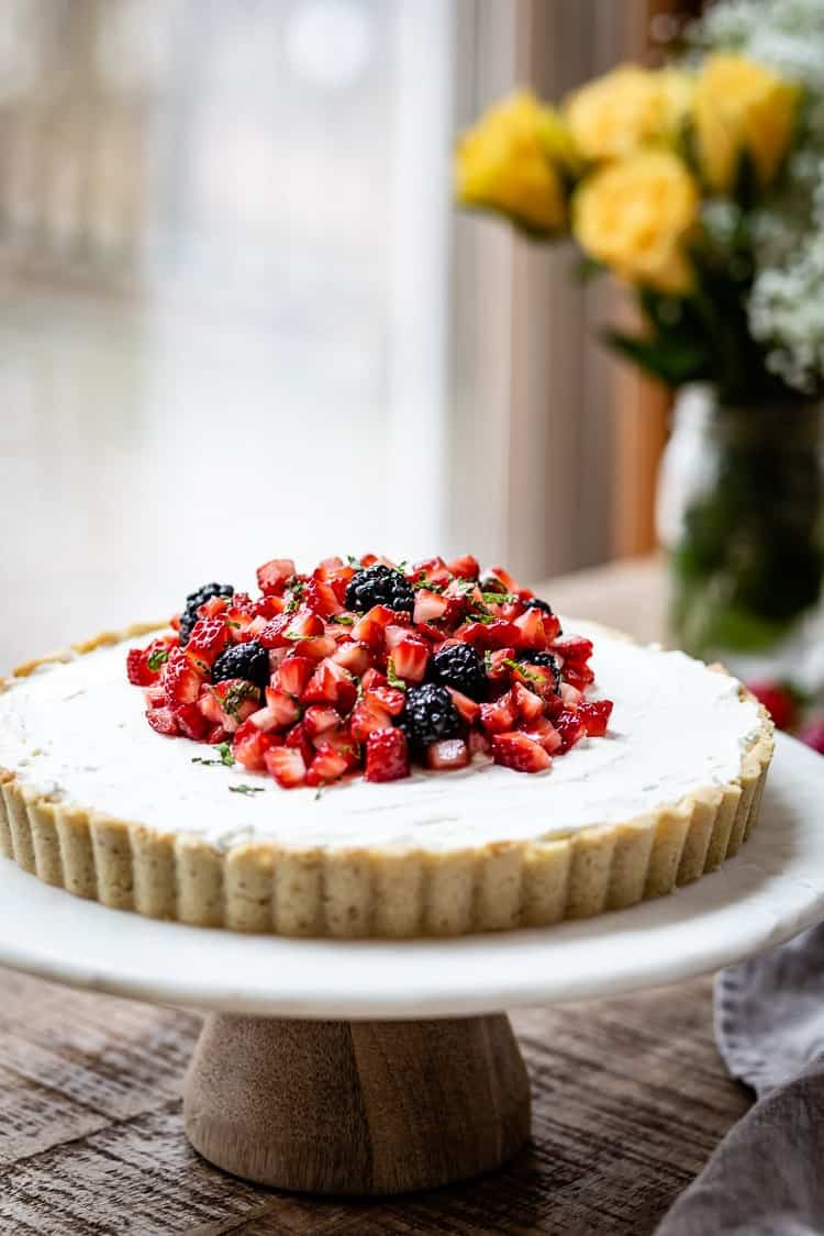 Strawberry and Mascarpone Tart with Gluten Free Almond Flour Tart Crust on a cake stand with roses in the background