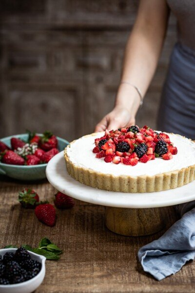 Strawberry Mascarpone Tart in almond flour crust being served by a woman