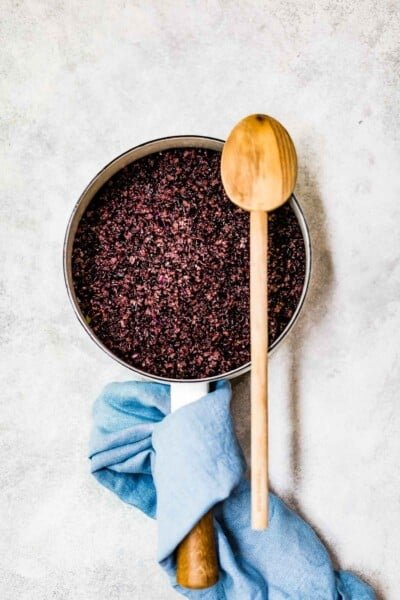 cooked black rice in a saucepan with a wooden spoon on the side