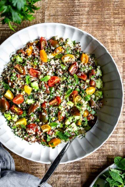 A big bowl of Quinoa Tabbouleh Salad with a spoon on the side