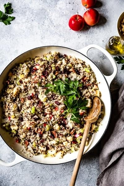 Quinoa, apple and cranberry stuffing for the best vegan stuffed acorn squash recipe in a large skillet from the top view