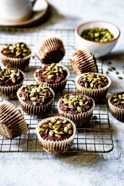 Paleo Pumpkin Muffins with almond flour cooling on a rack with pumpkin seeds on the side