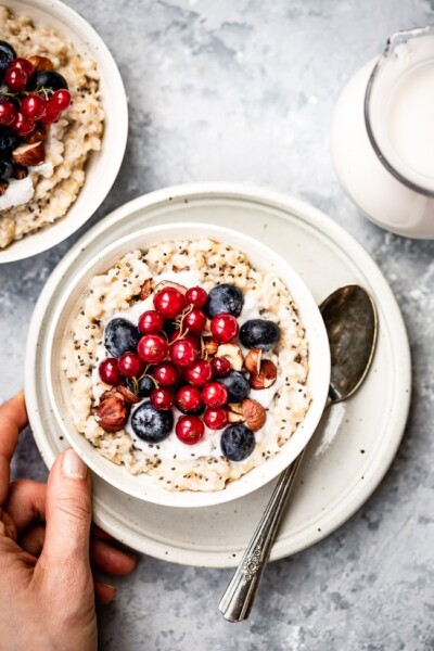 a woman is placing a bowl of Overnight Steel Cut Oats on a bowl