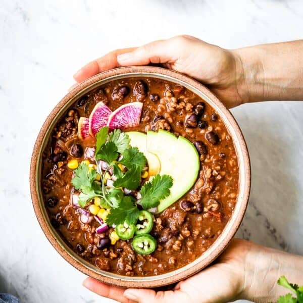 A big bowl of vegan chili topped off with avocados and cilantro photographed from the top view