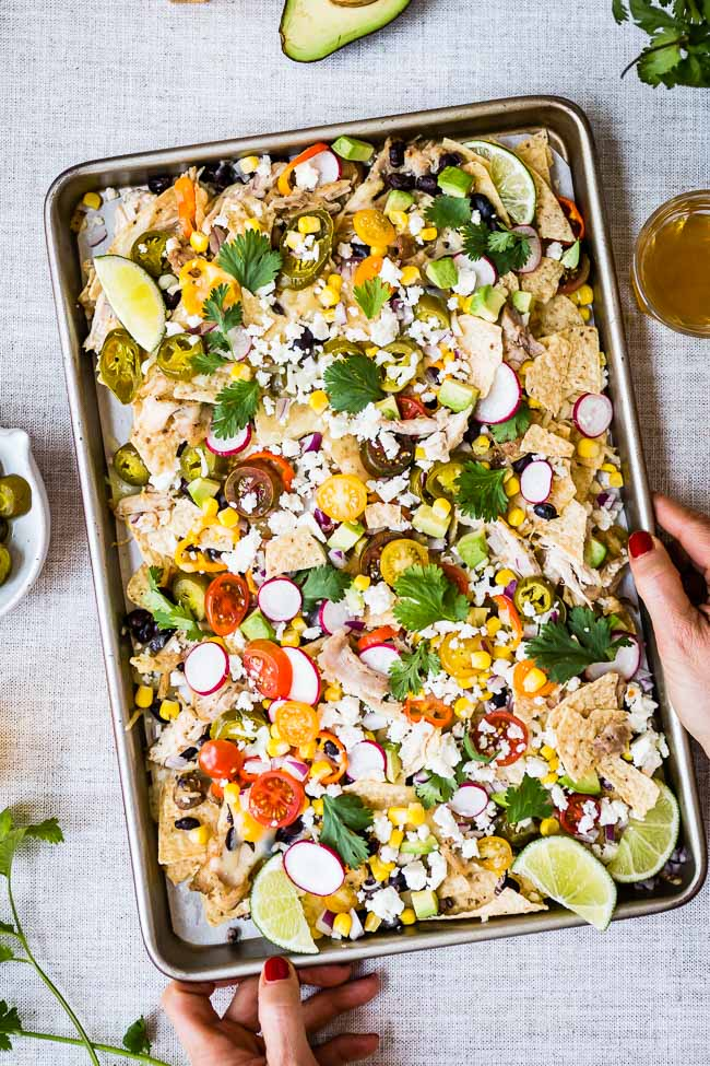 Healthy Game Day Ideas Including chicken nachos a woman is serving it