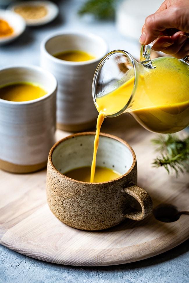 Golden Milk Tea being poured to a mug.